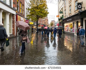 NOTTINGHAM, ENGLAND - NOVEMBER 21: Lots of people with umbrellas walking in rain past shops on Clumber Street in Nottingham. In Nottingham, England. On 21st November 2016.