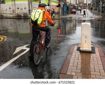 NOTTINGHAM, ENGLAND - NOVEMBER 21: Male cyclist wearing waterproof hi vis clothing at road junction on rainy day, Nottingham. In Nottingham, England. On 21st November 2016.