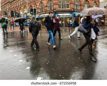 NOTTINGHAM, ENGLAND - NOVEMBER 21: Men commuting with take away coffee cups in rain in Nottingham, England. On Carrington Street, in Nottingham, England. On 21st November 2016.