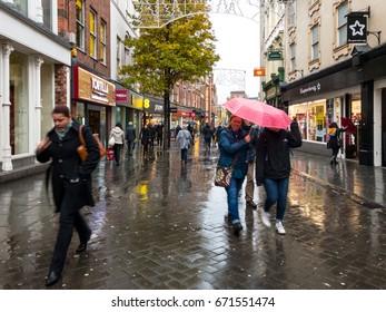 NOTTINGHAM, ENGLAND - NOVEMBER 21: People sheltering under unbrellas walking in rain past shops on Clumber Street in Nottingham. In Nottingham, England. On 21st November 2016.