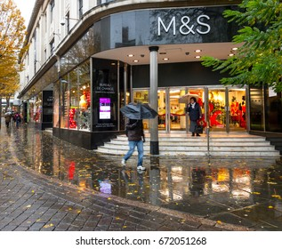 NOTTINGHAM, ENGLAND - NOVEMBER 21: People walking past Marks & Spencer, with umbrellas, rainy day, Nottingham. In Nottingham, England. On 21st November 2016.