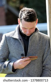 NOTTINGHAM RACECOURSE, COLWICK PARK, NOTTINGHAM, UK : 10 APRIL 2019 : Racehorse Trainer David Loughnane checks his mobile phone at Nottingham Races