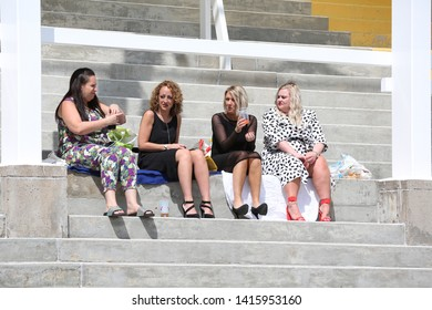 NOTTINGHAM RACECOURSE, NOTTINGHAM, UK : 11 MAY 2019 : Four ladies decide to sit on the concrete steps in the Grandstands during Ladies Day at Nottingham Races