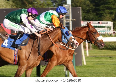 NOTTINGHAM RACECOURSE, NOTTINGHAM, UK : 17 JUNE 2019 : Racehorses gallop past the Winning Post together in a tight photo finish at Nottingham Races