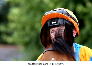 NOTTINGHAM RACECOURSE, NOTTINGHAM, UK : 19 JULY 2019 : Jockey Paul Hanagan hides behind the ears of his horse Kripke as he leaves the Parade Ring at Nottingham Races