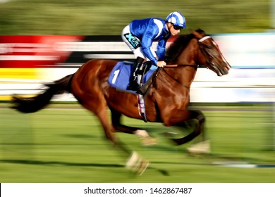 NOTTINGHAM RACECOURSE, NOTTINGHAM, UK : 6 JULY 2019 : Racehorses passing the Winning Post at Nottingham Racecourse - taken with slow shutter speed and camera pan for blurred effect and movement