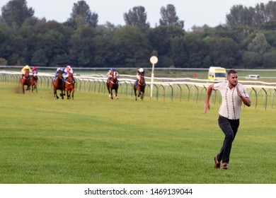 NOTTINGHAM RACECOURSE, NOTTINGHAM, UK : 6 JULY 2019 : An adult male member of the public invades the racetrack and runs in front of the racehorses during the finish of a race at Nottingham Races