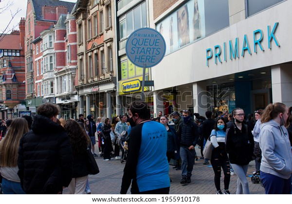 Nottingham. UK. April 14 2021. A large number of people are waiting to get into the clothing retail shop Primark, with a staff member holding a sign Queue Starts Here.