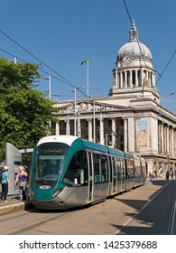 Nottingham UK - August 17, 2016 : New electric tram system carriage in Nottingham's Old Market Square with Council House building in the background, Nottingham City, England, UK. Editorial Image.