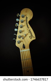NOTTINGHAM, UNITED KINGDOM - Mar 23, 2020: Fender Stratocaster electric guitar head stock and maple neck on black background, upto third fret visible with all tuning pegs and strings.