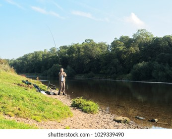 Nottinghamshire, England - September 11, 2015: A fisherman stands on the banks of the River Trent holding his fishing rod upright as he begins to cast his line out in to the river.