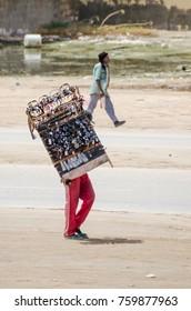 Nouakchott, Mauritania - October 08 2013: Street scene with sunglasses salesman walking down the road