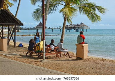 Noumea; New Caledonia - November 22, 2017: Melanesian people relaxing in the late afternoon sun at the Beach in Noumea, New Caledonia.