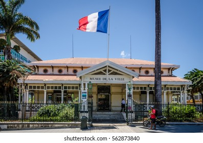 NOUMEA, NEW CALEDONIA â?? OCTOBER 29, 2016: The French flag files high above the city museum as a man with a bicycle walks along the black iron fence surrounding the building.