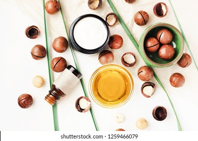 Nourishing aromatic macadamia nut oil & body butter, ingredients top view white table background. Vitamin rich natural skin treatment, essential oils.