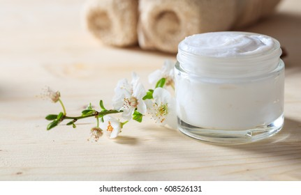 Nourishing face cream. Moisturizing natural cream and almond blossoms on wooden background