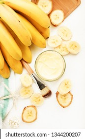 Nourishing homemade banana skincare mask, body butter in jar, ripe yellow fruits, vertical on white table, natural cosmetic ingredients top view.
