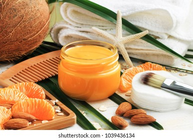 Nourishing natural skin care, bright fresh tangerine fruit slices, orange jar of aromatic facial cream, bathroom towels, ingredients for home spa beauty treatment.