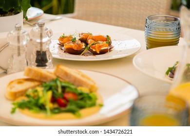 Nourishing snacks. Close up of tasty nourishing snacks and bruschetta near orange juice