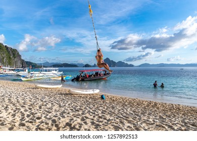 Nov 18,2018 A woman on a swing at the 7 commandos island beach in a El nido, Palawan, Philippines