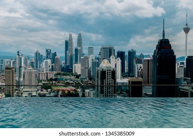 Nov 2018. Petronas Twin towers seen from skyscrapper's roof with pool, Kuala Lumpur central park, KLCC