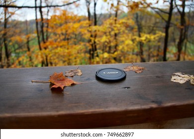 Nov 5th, 2017- Oakville, Canada: A canon lens cap on a wooden railing outdoors in a forrest during autumn