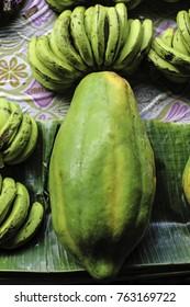 "nov2017, Honiara,Guadalcanal, Solomon Islands, the ""pawpaw king"" , papaya fruit and a bunch of bananas wait for customers in the main market"