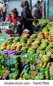 Nov,2017,central market, Honiara, Solomon Islands, two women sell their fruits in the central market in Honiara, they both look in opposite directions and one wears a red shawl around her neck