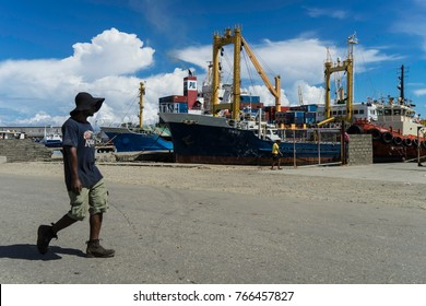 Nov2017,Point Cruz, Honiara, Solomon Islands, a lonely figure with a biggish sun protection hat walks in the harbour area on a quiet Sunday morning with inter island ships in the background