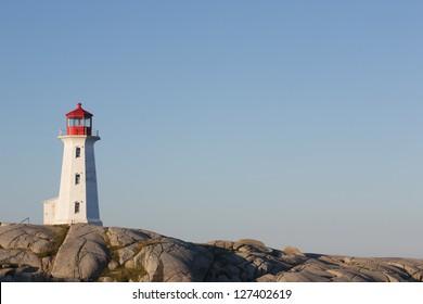 Nova Scotia's Peggys Cove lighthouse on a sunny day with blue sky.