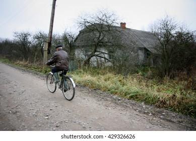 NOVA, UKRAINE - NOVEMBER 14 - Old man riding a bike on rural road near an abandoned house in Nova on November 14, 2008.