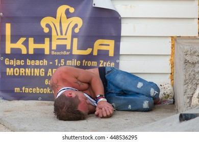 Novalja, Croatia, - July 24, 2015: Wasted drunk guy sleeping on floor after wild partying on hot summer day on Zrce beach, Novalja, Pag island, Croatia on July 24, 2015.
