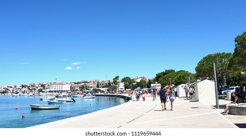 Novalja, Croatia, Jun 23, 2018. The waterfront in Novalja, with people walking around on a sunny summer day