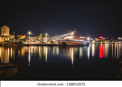 NOVALJA, PAG / CROATIA - 20, SEPTEMBER 2018. Night photo of  ship with a big light in the middle of the port with reflection in water. Bright City at night with small harbor and streets.