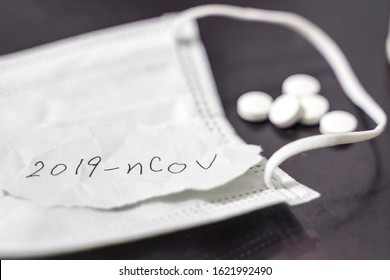 """Novel coronavirus disease named """"2019-nCoV"""" handwriting on paper with breathing mask and pill,selective focus on handwriting text."""