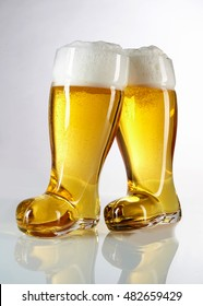 Novelty boot shaped beer glasses filled with frothy golden beer or lager in an Oktoberfest theme on a reflective white background