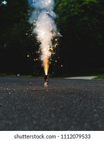 Novelty cake firework exploding on a quiet suburban street at night