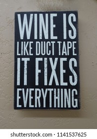 "A novelty comical sign with the saying ""Wine is like duct take it fixes everything""."