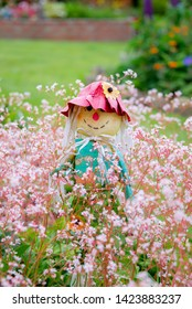 A novelty scarecrow garden ornament positioned on a stem in a flower bed within a domestic garden