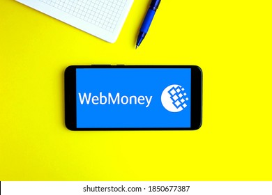November 08, 2020, Moscow, Russia. Electronic wallet WebMoney on the smartphone screen. Yellow background, telephone and notebook.