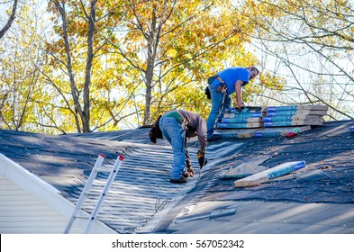 november 1, 2015, Michigan USA; workers repairing a roof by replacing singles and water barrier