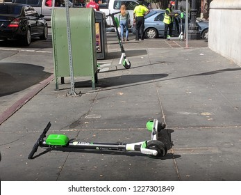 November 1, 2018 - Oakland, California: A dockless electric scooter is seen trashed along the sidewalk on a busy intersection of downtown Oakland.