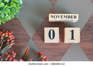 November 1. Date of November month. Number Cube with a flower and leaves on Diamond wood table for the background
