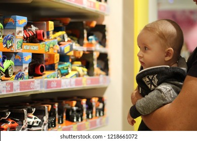 November 1, Ukraine Odessa, Epic store in Epicenter, a kid in a children's store in his arms at his father near the shelves with toy cars, selective focus.