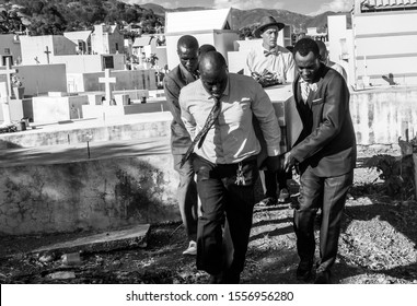 november 11, 2019. sabana larga, dominican republic. dramatic black and white group of Haitian men carrying a casket of friend at a cemetery.