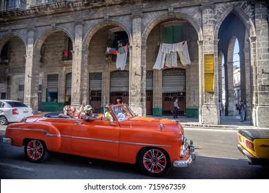 November 15, 2016, Havana, Cuba. Tourists taking a ride in a classic car on the streets of Havana Vieja.