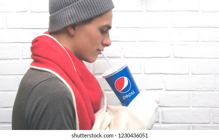 November 15, 2018. A young man drinks a Pepsi drink with a straw. Winter