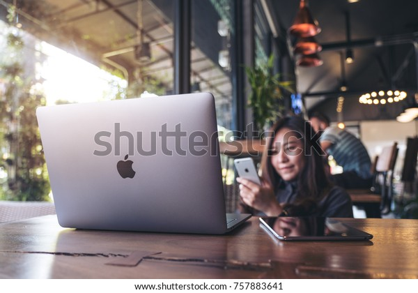 November 17th 2017 : A beautiful Asian business woman holding , using and looking at smart phone with laptop on wooden table in modern cafe , Chiangmai Thailand