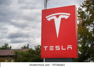 November 2, 2017 Sunnyvale/CA/USA - Tesla logo in front of a showroom located in San Francisco bay area; cloudy sky in the background