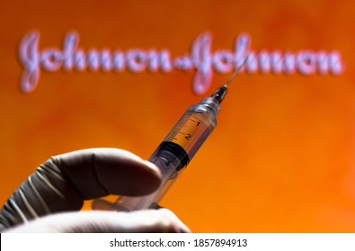 November 20, 2020, Brazil. In this photo illustration the medical syringe (coronavirus vaccine) is seen with Johnson and Johnson company logo displayed on a screen in the background